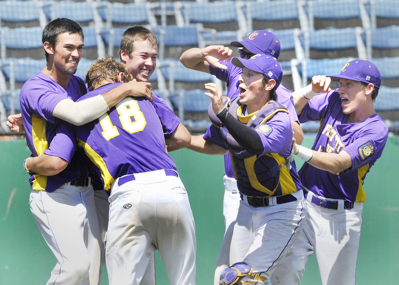 First Title's Harry Ridge, No. 18, gets a big welcome at home after scoring the winning run on a sacrifice fly by Drew Ferrick in the bottom of the ninth at The Ballpark in Old Orchard Beach on Monday.