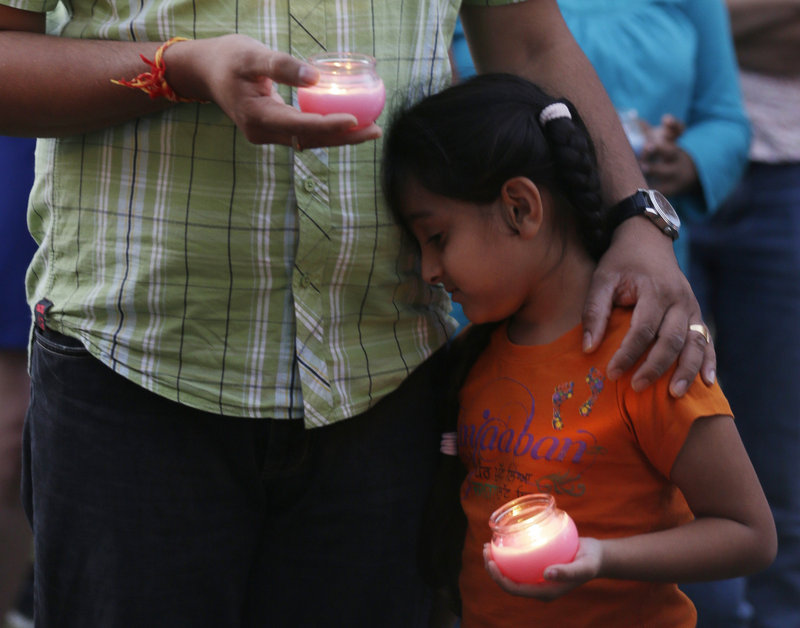 A man holds his child during a candlelight vigil for the victims of the Sikh temple shooting in Milwaukee on Sunday. Six members of the temple were killed.