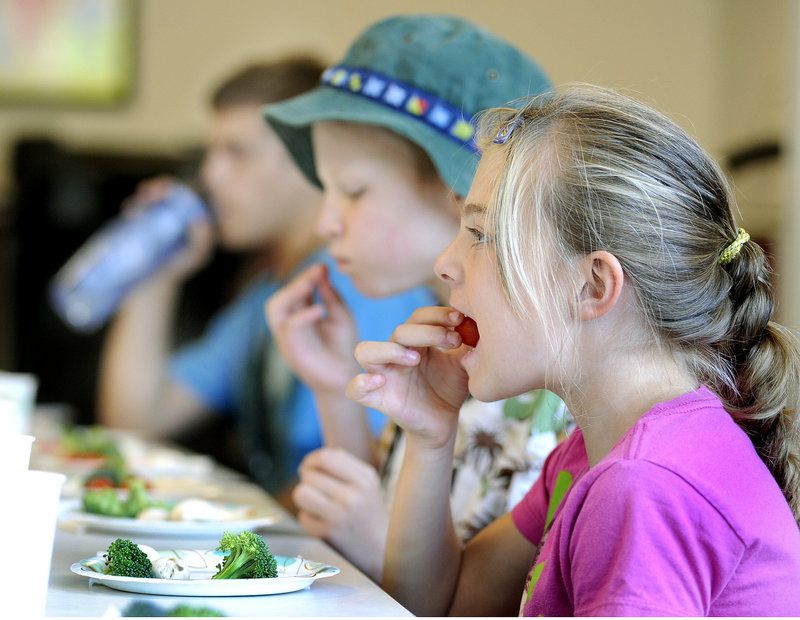 "Tamisa Ferrente, 7, samples a tomato during a CATCH Healthy Habits program at the South Portland Boys & Girls Club recently. The nutrition and exercise lessons include teaching the children to identify ""go"" foods, ""slow"" foods and ""whoa"" foods, ""go"" being the healthiest and ""whoa"" the least."