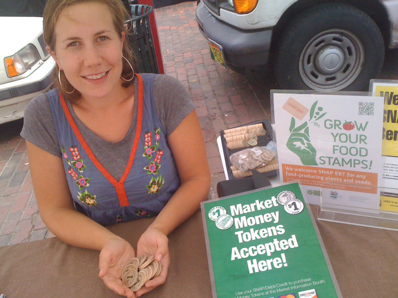 Dani Scherer, SNAP program staffer at the Portland Farmers Market, holds wooden tokens that food stamp recipients and credit and debit card users can obtain at the market information booth. The grant funding to support Scherer's position at the Wednesday and Saturday markets and pay for the electronic processing equipment and fees runs out at the end of August.
