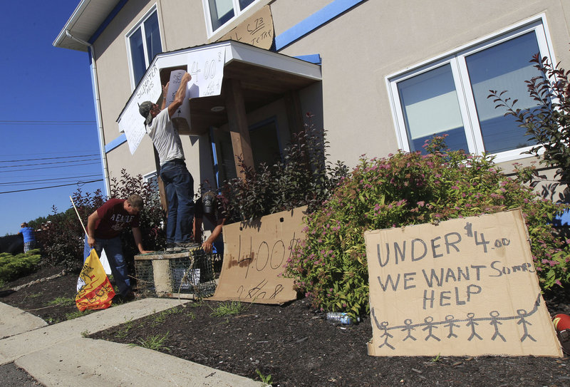 Protesters put up signs Wednesday outside the office of fisheries minister Keith Ashfield in Fredericton, New Brunswick. They are trying to get him to address the importing of cheap Maine lobster that makes it hard for Canadian lobstermen to compete and earn a profit.