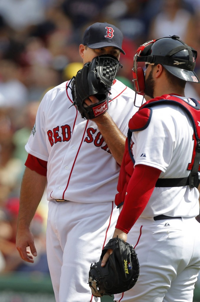 Josh Beckett chats with catcher Kelly Shoppach during the third inning Wednesday at Fenway Park. Beckett was roughed up in a 10-9 loss to Texas.