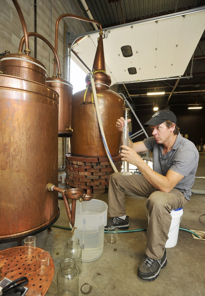 Distiller Tim Fisher uses a hydrometer to measure the alcohol content of rum coming out of New England Distilling's copper still, which was made in Portugal, and which Wight designed himself.
