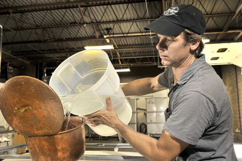 Tim Fisher pours recently distilled rum into a holding tank.
