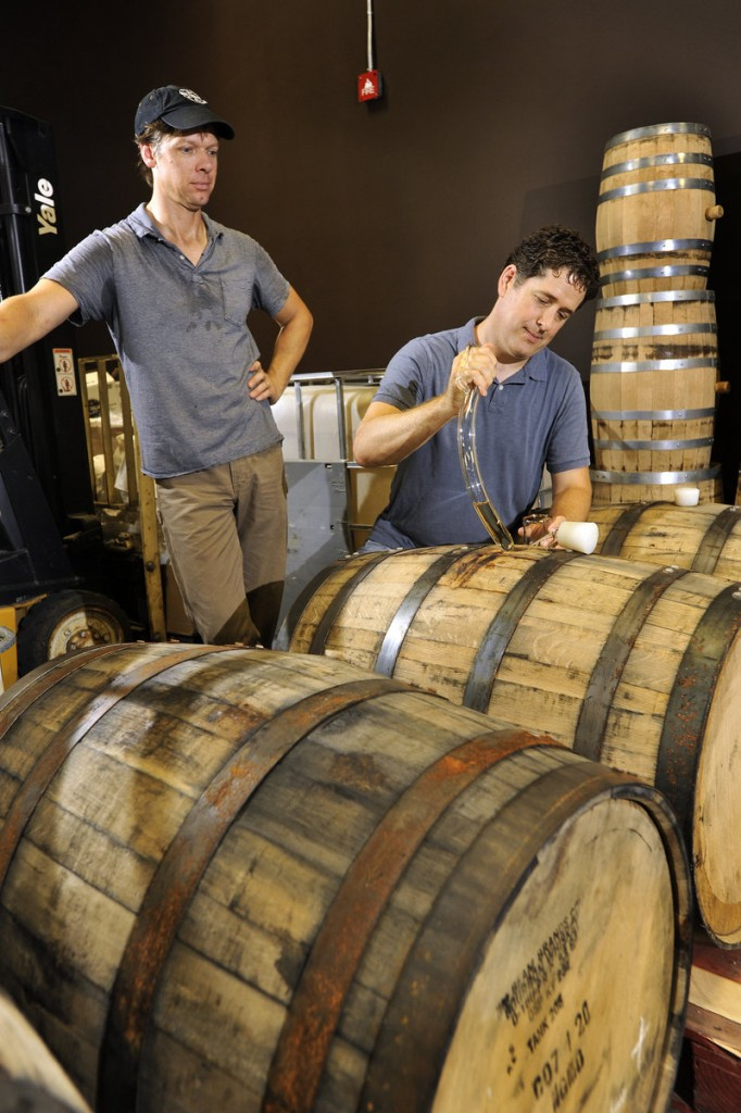 "Distiller Tim Fisher, left, watches as Ned Wight uses a ""barrel thief"" to sample a batch of rum."