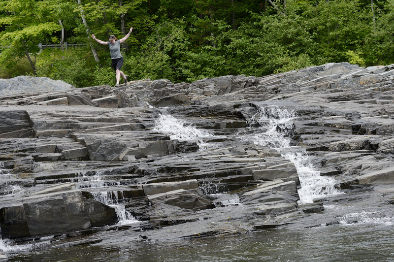 Maine Sunday Telegram staff writer Deirdre Fleming navigates the rocks while exploring Big Wilson Falls, one of more than 100 picturesque waterfalls in Piscataquis County.
