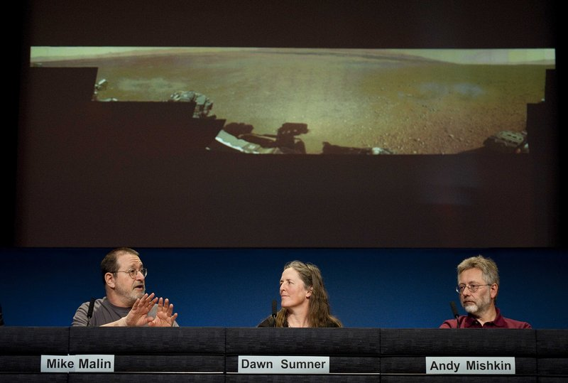 Michael Malin of Malin Space Science Systems, San Diego, left, talks next to Dawn Sumner, University of California, Davis, and Andy Mishkin of NASA's Jet Propulsion Laboratory, about a low-resolution panoramic image of Mars, background, during a news conference Thursday.