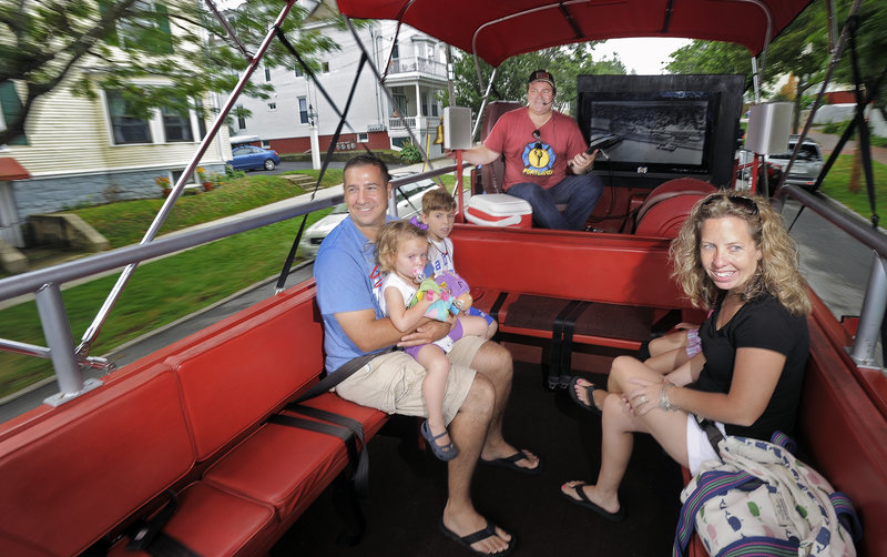 Ken Araujo and his family, residents of Acushnet, Mass., ride aboard a converted 1971 International Harvester fire truck on Friday during a tour conducted by Tim Lambert of the Portland Fire Engine Co.