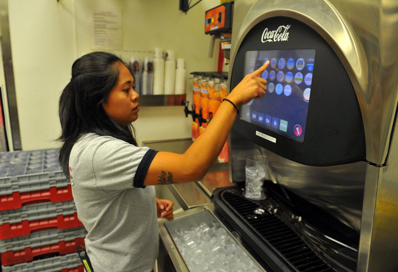 Junabelle Devega, a server at a Taco Mac in Sandy Springs, Ga., uses a Coca-Cola Freestyle fountain dispenser. The computerized drink machines dispense combinations of more than 120 of the company's brands.