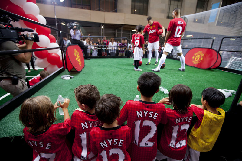 Children gather to watch Manchester United performers outside the New York Stock Exchange on Friday. The soccer club is the best-known sports team in the world, but its finances are less sterling: It is hundreds of millions of dollars in debt.