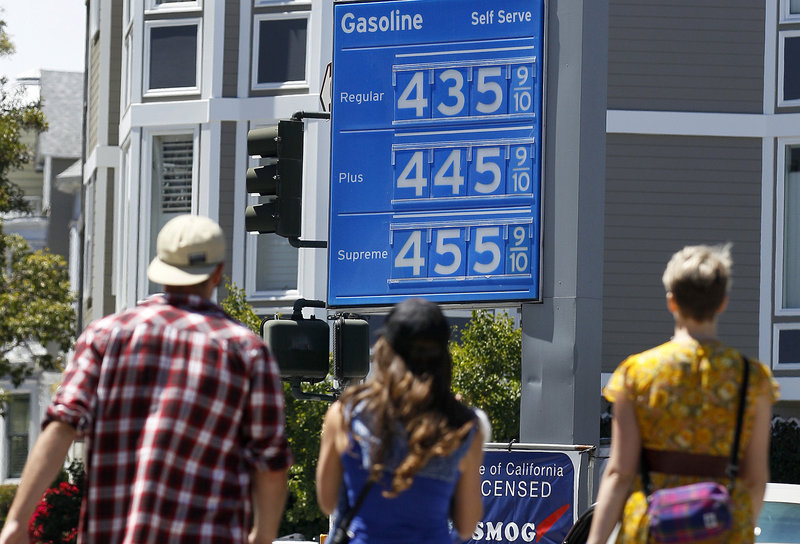 Pedestrians walk toward a Chevron gas station price board in San Francisco on Friday. Analysts say that without any further disruptions, such as refinery problems or hurricanes in the Gulf of Mexico, gasoline will probably begin dropping after Labor Day as refiners switch to cheaper blends and drivers hit the road less often.