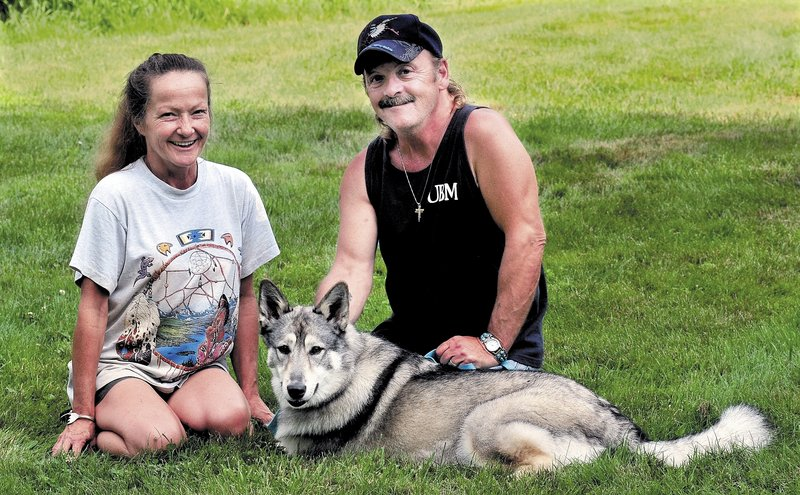 Julie and Gene Mitchell of Detroit with their 2-year-old wolf hybrid named Wolf.