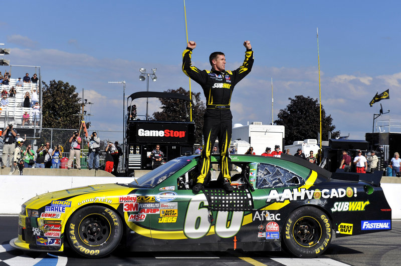 Carl Edwards stands atop his car after winning the Nationwide Series race at Watkins Glen, N.Y., on Saturday. Edwards, running his first Nationwide race this season, held off fellow Sprint Cup driver Brad Keselowski.