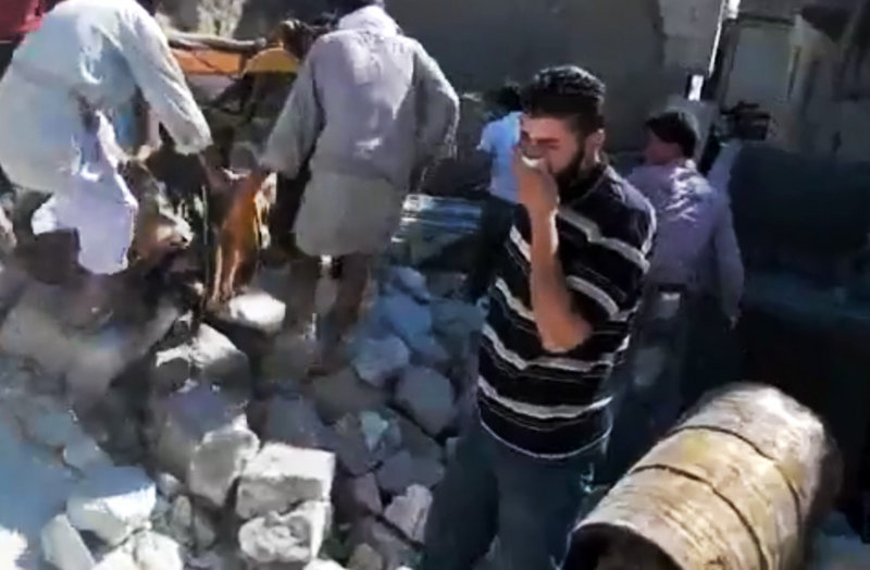 Image made from amateur video accessed Sunday purports to show a Syrian man reacting after other men, left, lifted a body from the rubble of a building destroyed by Syrian forces shelling Kfarnebel, in Idlib province, northern Syria.