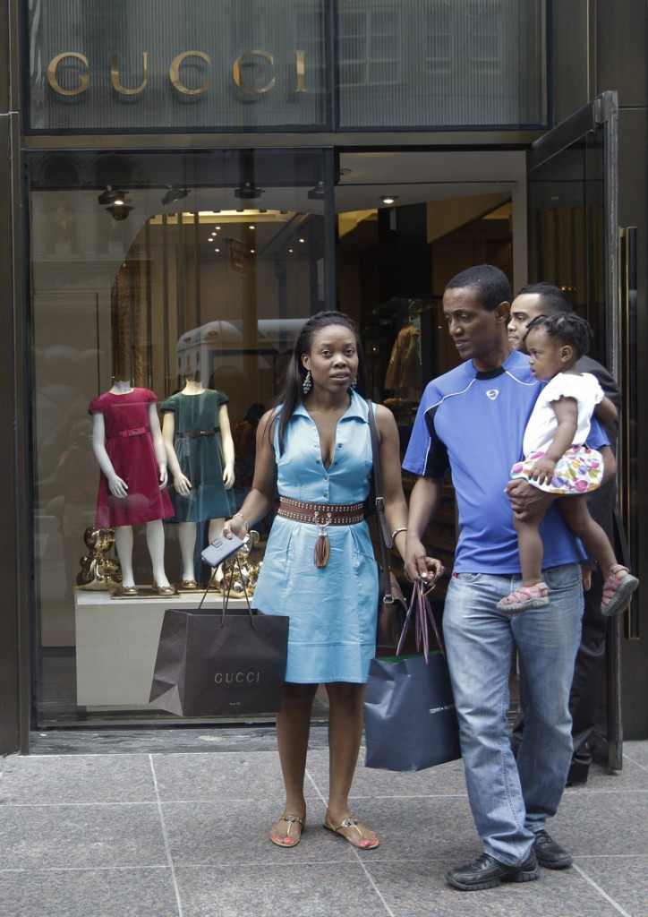 A couple leaves the Gucci children's boutique on Fifth Avenue in New York. Children's fashion designers are targeting households with incomes of at least $350,000, says an industry analyst.