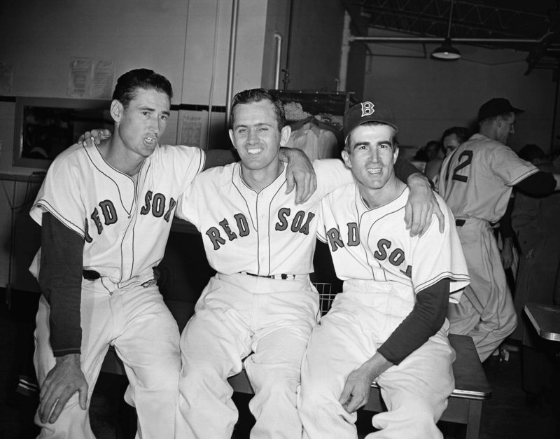 Boston Red Sox pitcher Mel Parnell, center, is flanked by teammates Ted Williams, left, and Johnny Pesky after a 4-1 win over the New York Yankees at Fenway Park in 1949. Pesky, who spent most of his 60-plus years in pro baseball with the Red Sox, was beloved by the team's fans, and the right-field foul pole at Fenway is named after him.