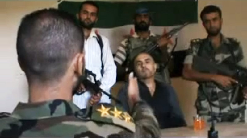 Image made from amateur video purports to show Syrian Col. Rafik Mohammed Suleiman being interrogated by a rebel officer after his Soviet-made MiG warplane was apparently hit by ground fire over Deir el-Zour province.