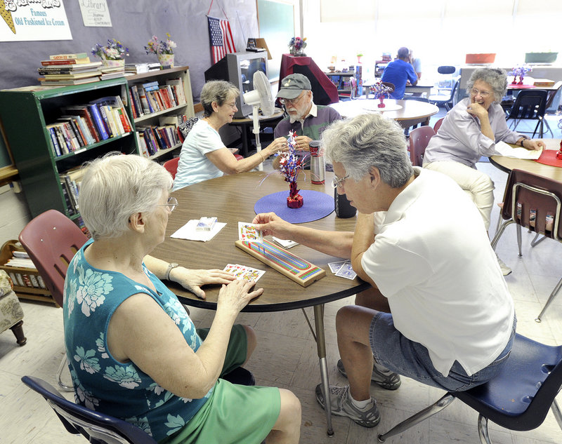 Ethel Blake and Rosemary Holleman, pictured here earlier this week, are among the seniors who enjoy playing cards and socializing at the Lakes Region Senior Center inside the Gorham Activity Center in Gorham. The group now has more than 100 members – and less than a year to find a new place to meet.