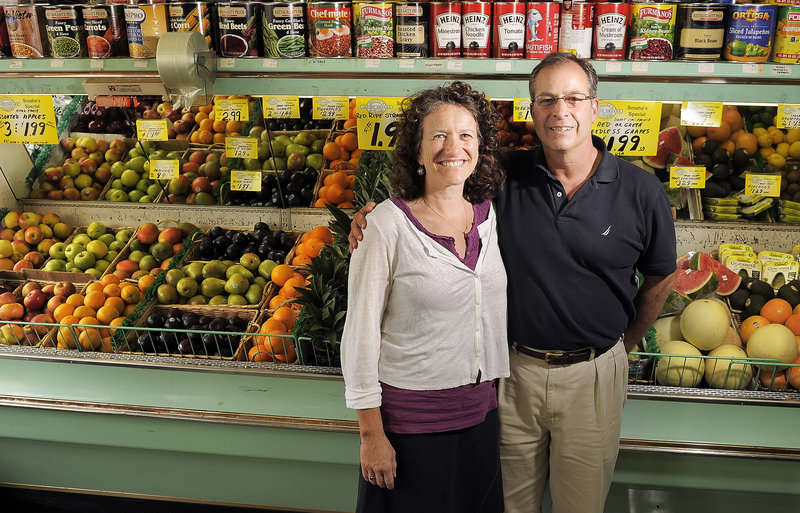 Alan Cardinal joins his wife, Sylvia Most, on Tuesday at Smaha's Legion Square Market in South Portland. They will operate the grocery store and butcher shop together.