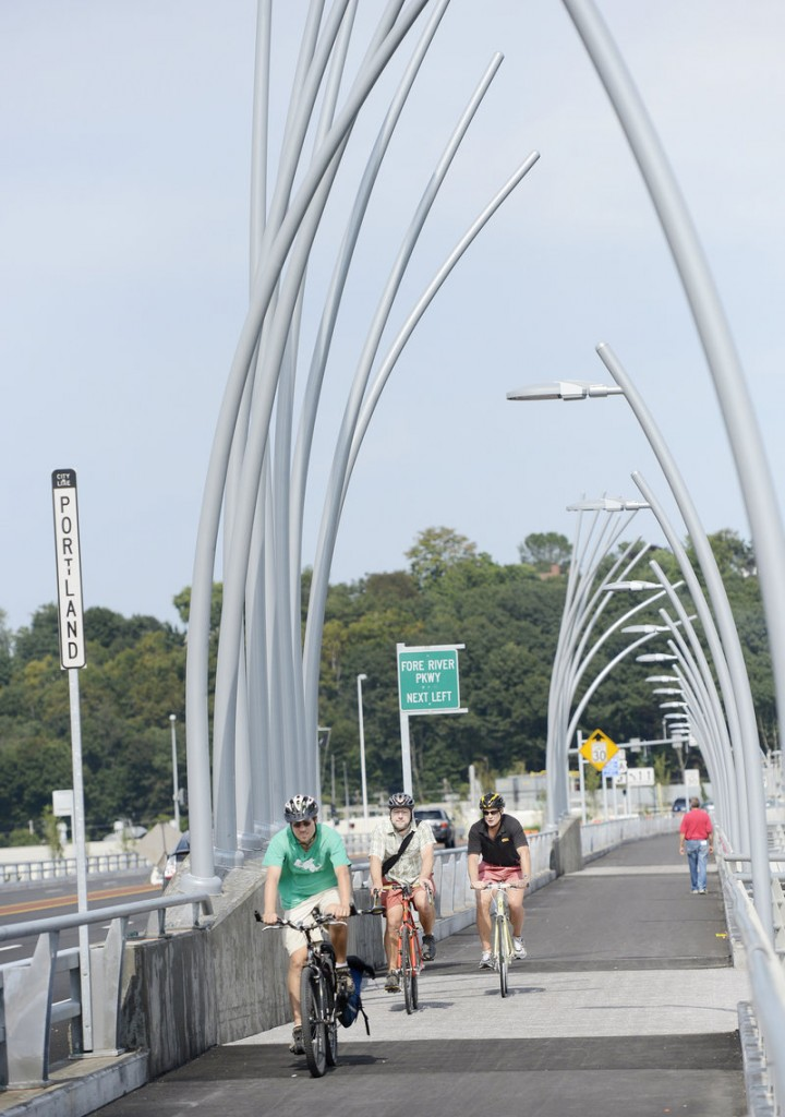 Bicyclists, including, left to right, Phil Goff of Arlington, Mass., Carl Eppich of South Portland and Paul Niehoff of Portland pedal past reed poles, an artistic element of the Veterans Memorial Bridge over the Fore River.