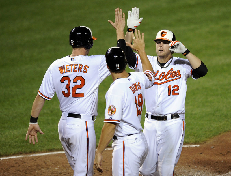 Baltimore's Mark Reynolds gets a welcome after his three-run home run in the Orioles' 7-1 win over Boston Tuesday at Camden Yards. Reynolds' blast, his second of the game, came on the first pitch from reliever Mark Melancon.