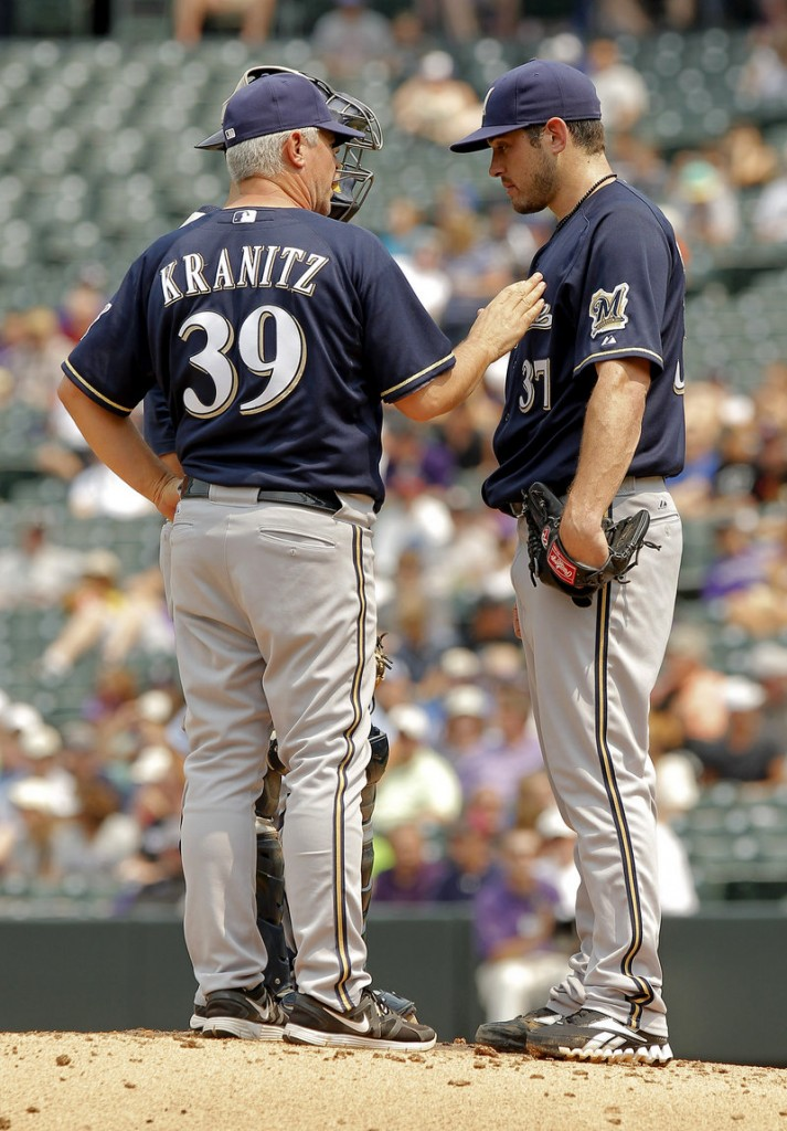 Milwaukee pitching coach Rick Kranitz confers with pitcher Mark Rogers as the Rockies scored three runs in the first inning and went on to win 7-6 at Denver.