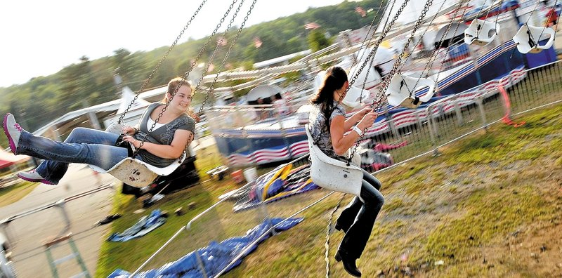 Michael G. Seamans/Morning Sentinel Krista Rogers, 19, left, and Megan Miville, 19, both of Fairfield, spin around on the Trapeze Swings at the Skowhegan State Fair on Wednesday.