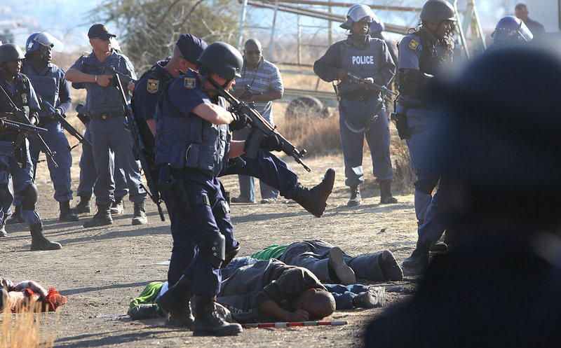 Police surround the bodies of striking miners after opening fire on a crowd Thursday at the Lonmin Platinum Mine near Rustenburg, South Africa. Up to 18 people were killed.