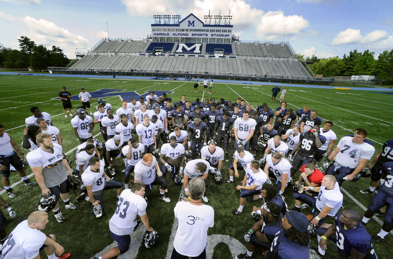 Practice is over for the day Friday, and University of Maine football coach Jack Cosgrove huddles with his players. The Black Bears are completing their first week of practice in preparation for the opener Sept. 8 at Boston College.