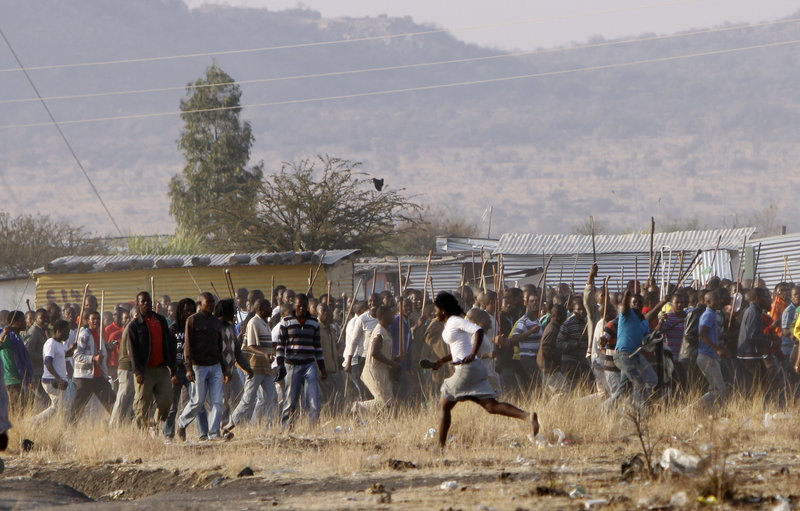 A woman runs in front of striking mine workers during tense moments at the Lonmin mine near Rustenburg, South Africa, on Friday. Some miners vowed a fight to the death Friday as police announced the death toll of 34 from the previous day.