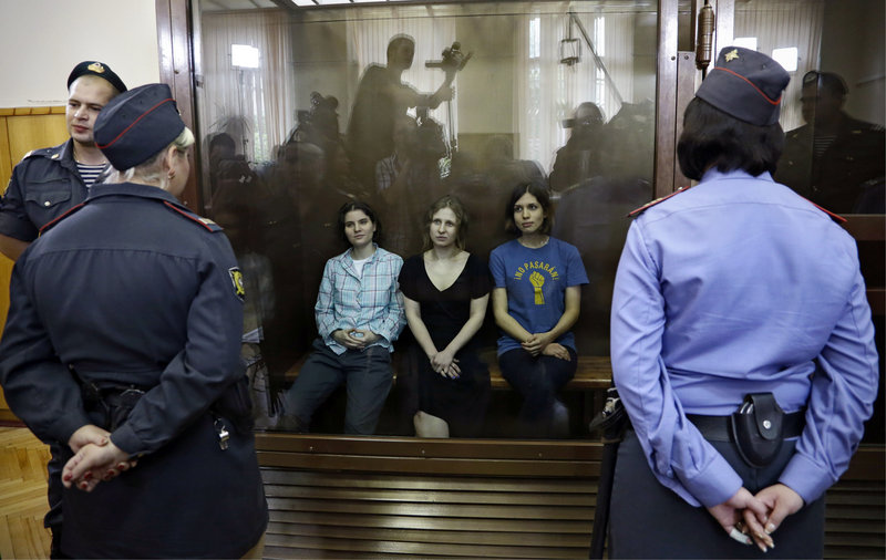 Members of the feminist punk group Pussy Riot, from left, Yekaterina Samutsevich, Maria Alekhina and Nadezhda Tolokonnikova sit in a glass cage in a Moscow courtroom Friday. They were convicted of hooliganism.