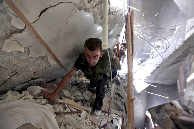 Syrian fighters search for survivors under the rubble of a building destroyed in an airstrike in Aleppo, Syria, on Friday. Rebels have sought to control the city's center.