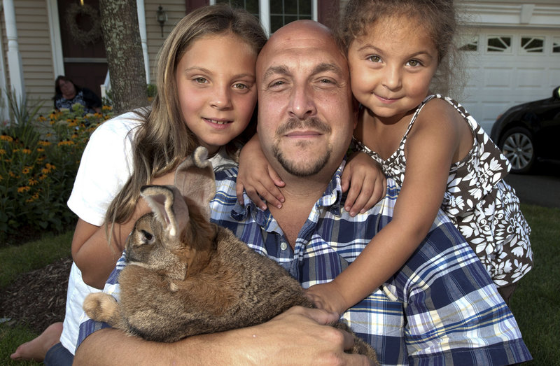 Kayden Lidsky, left, is shown with her father, Josh, sister Madison and Sandy, the family bunny, in North Haven, Conn.