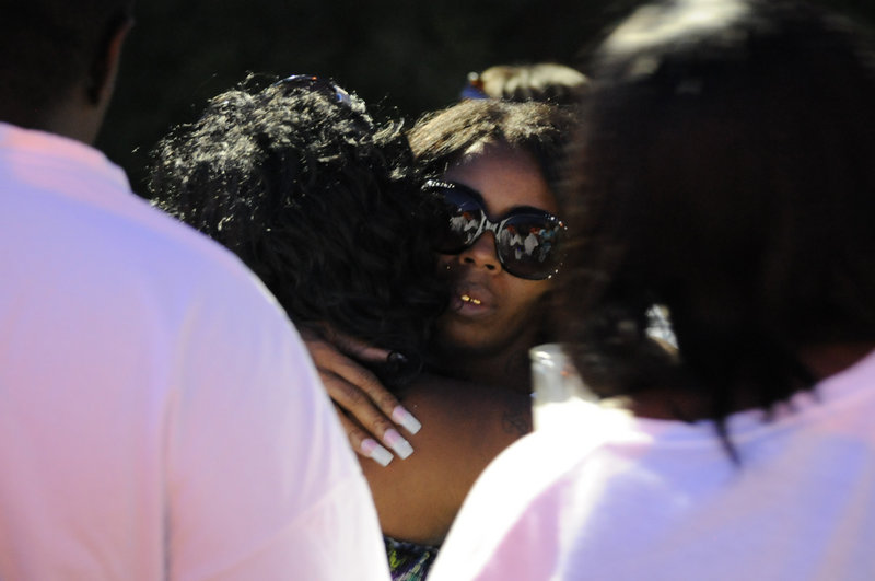 Teresa Carter, mother of Chavis Carter, is hugged by supporters after a candlelight vigil held Aug. 6 in her son's honor in Jonesboro, Ark. Police video, released under the Freedom of Information Act, hasn't resolved questions about whether he shot himself in the head as officers said.