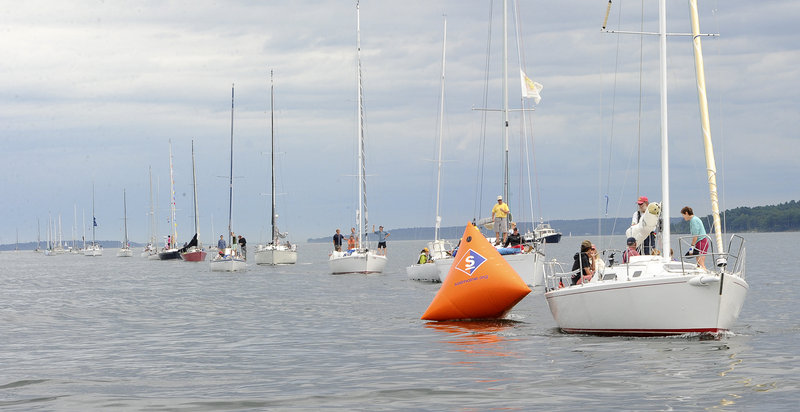 A parade of sailboats stretches down Casco Bay before the racing gets under way on Saturday. The annual Harborfest raises money for the National Multiple Sclerosis Society.