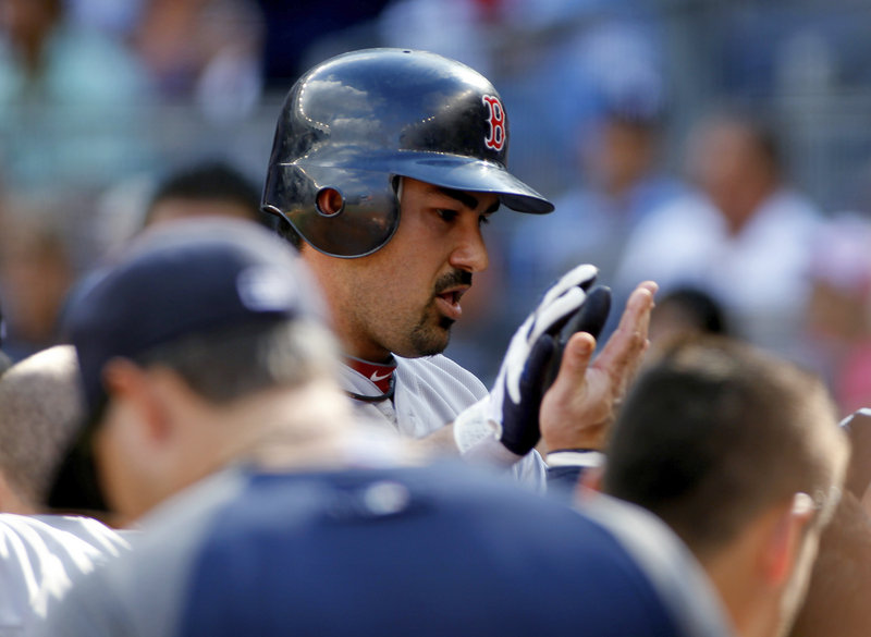 Adrian Gonzalez is welcomed back to the dugout by Red Sox teammates after hitting a two-run homer off David Phelps of the Yankees in the first inning.