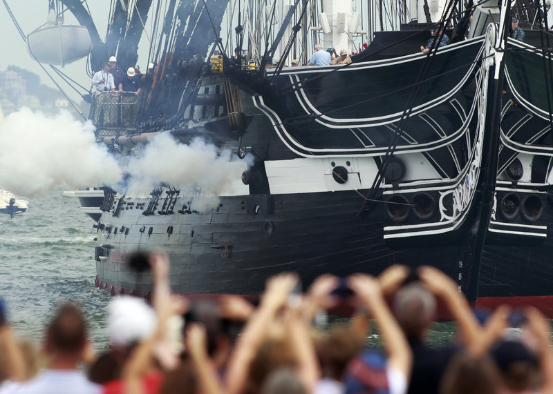 The USS Constitution fires one of its guns in Boston Harbor as a crowd looks on from the shore Sunday.