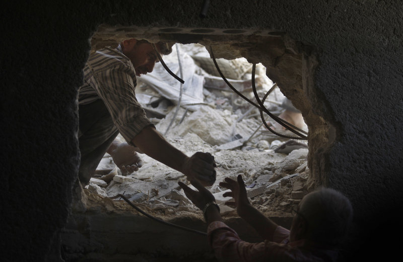 On Sunday, two men look for the bodies of two girls, ages 2 and 14, thought to be buried under the rubble of a building hit by a Syrian government airstrike in Aleppo.