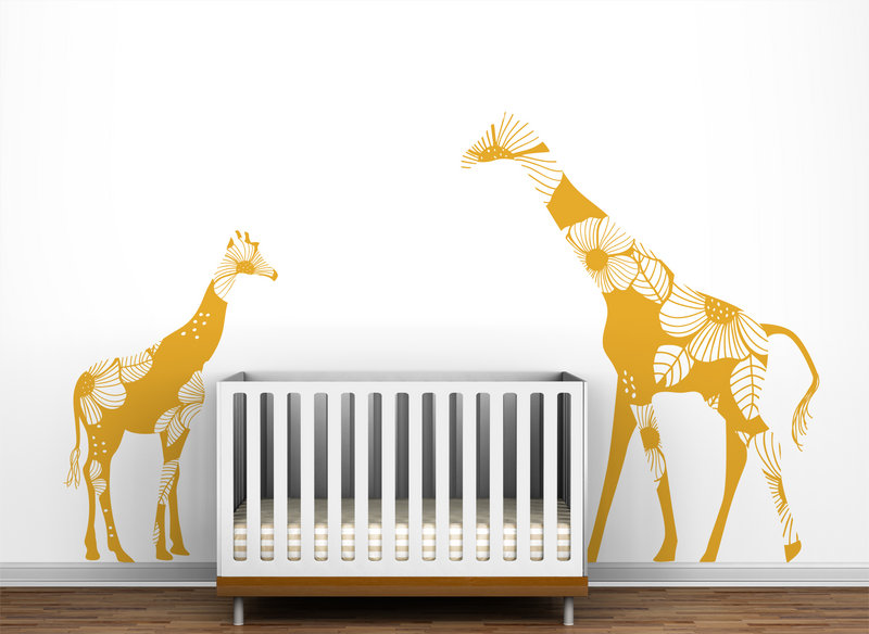 Giraffe wall decals from Little Lion Studio appear to watch over a crib.