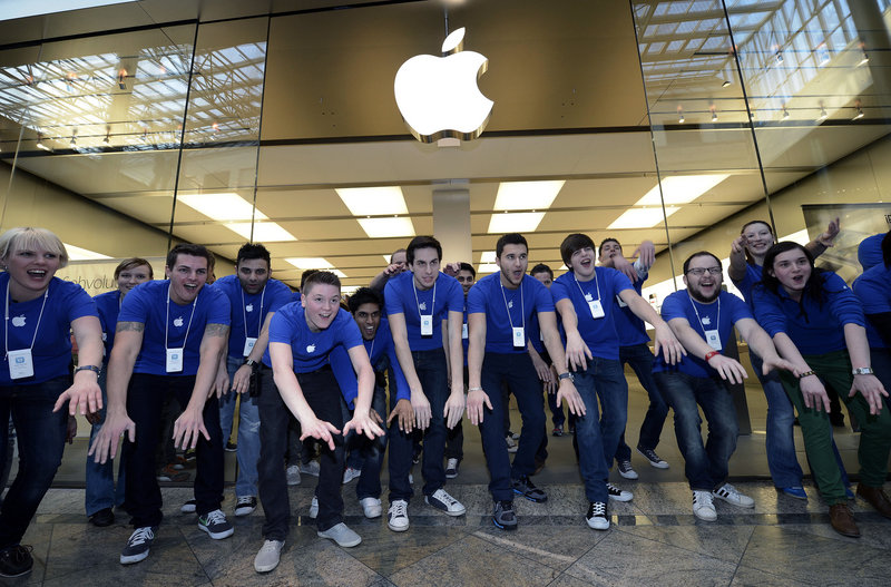 Apple employees greet customers in front of an Apple store in Oberhausen, western Germany, in March as the new iPad goes on sale there. On Monday, Apple set a new record for Wall Street's most valuable company, riding on optimism about a possible impending iPhone 5 launch.