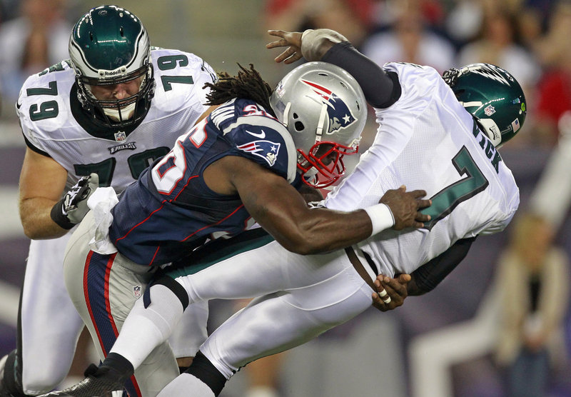Jermaine Cunningham of the Patriots levels Eagles QB Michael Vick in Monday night's preseason game at Foxborough, Mass. Vick left the game after the hit and had X-rays on his ribs, which were negative. The Eagles won without him, 27-17.