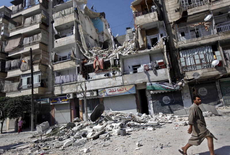 A Syrian man walks by a building destroyed in an airstrike in Aleppo, Syria, last Friday. The growing use of air power by the Syrian regime is causing a spike in civilian casualties.