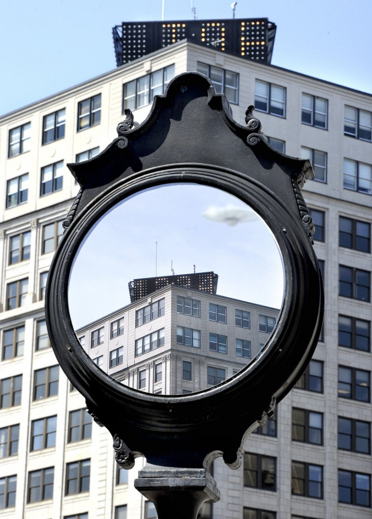 A clock in Portland's Monument Square is covered by a painting that looks like a mirror reflecting the top of the Time and Temperature building, with a UFO hovering nearby.