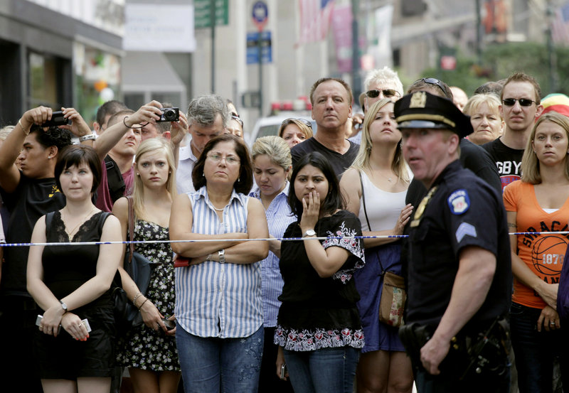 Bystanders and a police officer stand on Fifth Avenue after a shooting outside the Empire State Building in New York on Friday. One man and the gunman died, and nine others were wounded. A law enforcement official said the shooting was related to a workplace dispute.