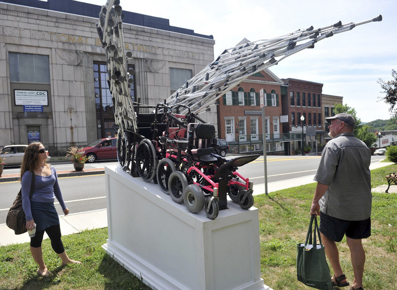 Daniel Turner takes a look at a sculpture by James Kitchen on display on the Town Common in Greenfield, Mass. The sculpture will be moved to Springfield in September.