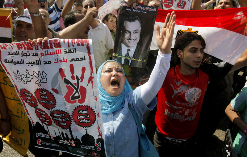 Anti-Muslim Brotherhood protesters hold posters of the late President Gamal Abdel Nasser in Cairo, Egypt, on Friday.