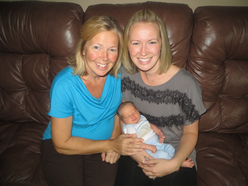 Madden Hebert rests with his mom, Angel Hebert, right, and his grandmother, Linda Sirois. Sirois carried the baby for her daughter, who has a heart condition.
