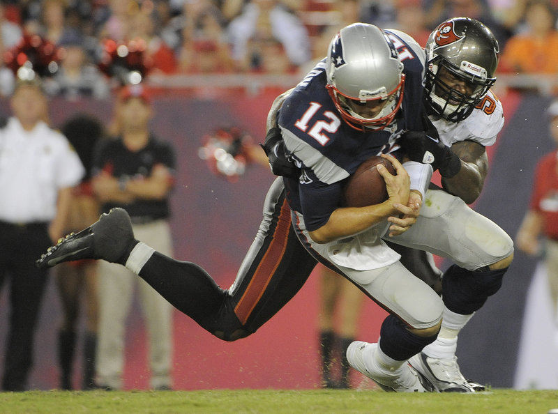 New England's Tom Brady is sacked by Tampa Bay's Adam Hayward during first-half action of their NFL preseason football game Friday night in Tampa, Fla. Brady threw one touchdown and had one interception in three quarters.