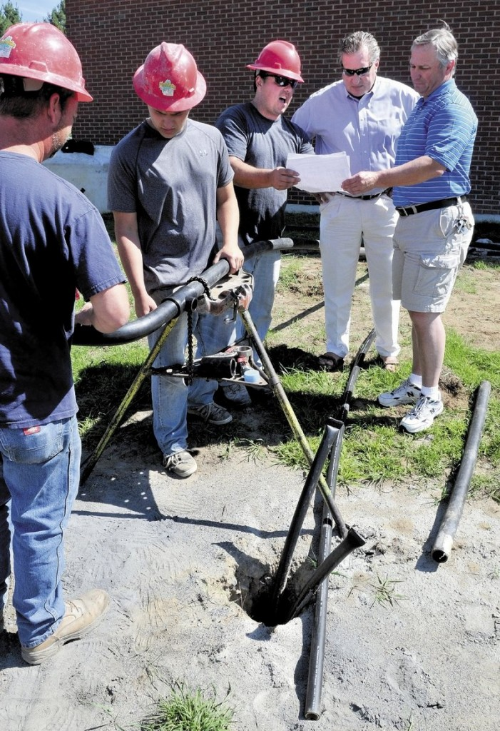 Grignon, center, explains the system being installed at the school to Superintendent Todd LeRoy and Principal Steve Ouellette last week, while Alan Grill, left, and Antoine Grignon install the piping system.