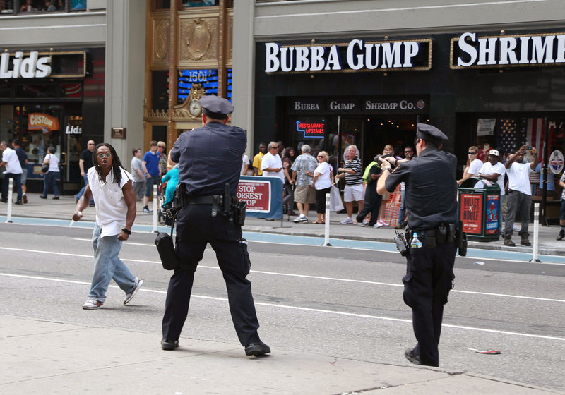 Police and a man wielding an 11-inch knife confront each other in New York's Times Square on Aug. 11. The man, identified as Darrius Kennedy of Hempstead, N.Y., a native of South Carolina, was shot dead by police a few blocks farther downtown.